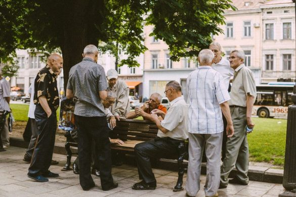 A group of senior citizens gathered near a bench